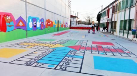 Padres y alumnos del colegio de Tinajas decoran el patio pintando en el suelo juegos tradicionales